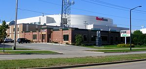 "WLUK-TV - Present day image of WLUK's facility, with the building since expanded to accommodate a news and content center and signage altered to recognize its sister station, WCWF. An ""Oneida Nation Walk of Legends"" monument to Packers player Jerry Kramer stands on the building's front lawn."