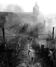 US soldiers advance through the hazy ruins of Waldenburg Germany, April 1945.