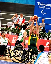 an athlete tilts his wheelchair and raises an arm to block his opponent's shot