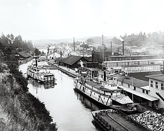 Willamette Falls Locks - The Willamette Canal and locks, looking north towards the Oregon City suspension bridge.  The steamer N.R. Lang is on the right.  By this date, sometime after 1900, a large concentration of industry has arisen just to the east of the canal.