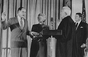 William Rehnquist (left) takes the oath as Chief Justice from retiring Chief Justice Warren Burger in 1986, as his wife, Natalie, holds the Bible and President Ronald Reagan (far right, by flag) looks on.