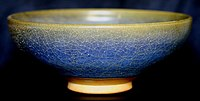A ceramic bowl is viewed from one side. The glaze has a crazed and mottled finish, varying from yellow at the rim of the bowl to blue below.