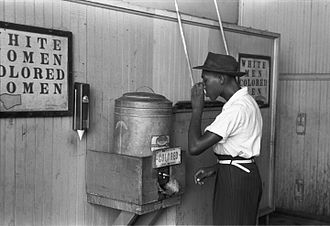 "Racial segregation in the United States - An African-American man drinking at a ""colored"" drinking fountain in a streetcar terminal in Oklahoma City, 1939."