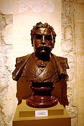 Foto van een buste van een streng uitziende man met een snor