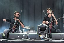 Two men playing cellos on a stage.