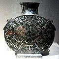 Photographie montrant une vasque dont le corps sphérique est orné de décor incrusté en argent.