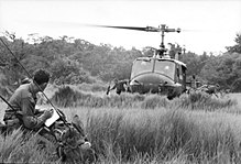 Black and white photo of a man wearing military uniform looking towards a helicopter on the ground from which two other men are moving away from