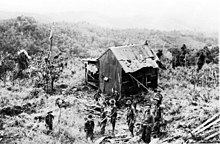 Soldiers stand in front of a dilapidated shed