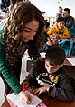 A Lebanese teacher lends a hand to Syrian children in Zaatari, Jordan (cropped).jpg