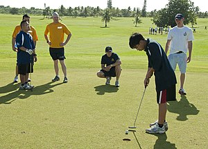 A Special Olympics athlete putts a golf ball as volunteers look on during the 2nd annual Special Olympics of Guam golf exhibition at the Admiral Nimitz golf course in Barrigada, Guam, Dec 111217-N-AZ907-005.jpg