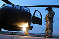 A U.S. Army UH-60 Black Hawk helicopter crew member assigned to the Puerto Rico Army National Guard inspects the aircraft prior to conducting night flight training at the aviation support facility in Isla 140902-Z-KD550-759.jpg