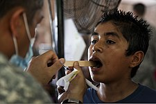 A U.S. Soldier, left, assigned to Joint Task Force Jaguar gives a dental screening to a boy during Beyond the Horizon (BTH) 2013 in Metalio, El Salvador, May 18, 2013 130518-A-IA672-087.jpg