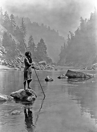 "Trinity River (California) - A Hupa man fishes at the ""Sugar Bowl"" rapids on the Trinity River, c. 1923."