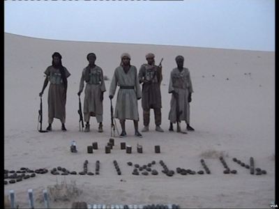Al-Qaida in Magreb members pose with weapons. Al-Qaida au Maghreb Islamique combattants.png