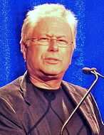 Photo of a male with balding white hair. He is wearing a black jacket.
