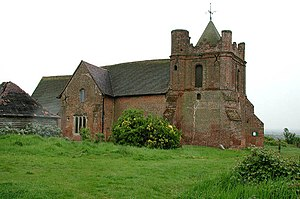 A stone church seen from the northwest, showing a squat tower with turrets on the top corners and a pyramidal roof; a transept protrudes from the centre of the church and part of the listed stable is on the extreme left