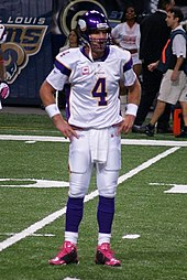 "A white man wearing a white and purple American football uniform. His helmet and the trim on the sleeves of his jersey are purple and there is a large numeral ""4"" in purple on his chest."