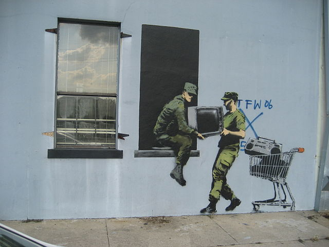 Grafitti in the Banksy-style of two military men stealing a TV