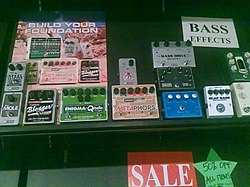 A music store display of effect pedals for bass is shown. The pedals have foot-operated switches to turn the effect on an off and knobs for controlling the tone.