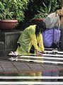 Beggar with Rain wear in Entrance of NTU Hospital West Site 20170509.jpg