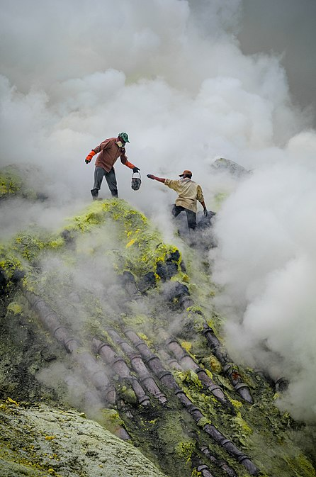 Traditional sulfur mining at Ijen Volcano, East Java, Indonesia. This image shows the dangerous and rugged conditions the miners face, including toxic smoke and high drops, as well as their lack of protective equipment. The pipes over which they are standing are for condensing sulfur vapors. Bergelut dengan asap nan beracun.jpg