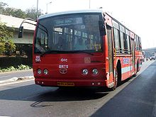A red bus on a road. Blue letters are seen on its side