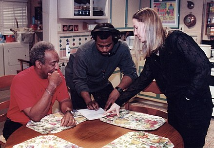 Cosby, a production assistant, and Ginna Marston of Partnership for Drug-Free Kids review the script for a 1990 public service spot at Cosby's studio in Astoria, Queens. Bill Cosby (left) production assistant (center) Ginna Marston (right).jpg