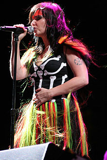 Björk is holding a mic in her right hand.