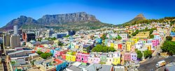 Bo-Kaap area of Cape Town with its distinctive pastel coloured houses in the foreground with the city centre to the left and Table Mountain in the background