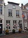 Huis met gebosseerd gepleisterde lijstgevel met platte voluten op de hoeken; met rode pannen belegd schilddak