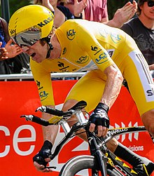 Bradley Wiggins riding a time trial bicycle wearing yellow cycling clothing.
