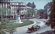 Period photo of thousands of armed soldiers marching down a city street and around a circular park, while a horse and carriage and car pass in the opposite direction
