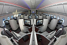 Airliner cabin with pod-like seats arranged in pairs or alone against the widewalls.