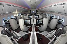 Cabine d'avion de ligne avec sièges en forme de nacelle disposés par paires ou seuls contre les larges parois.