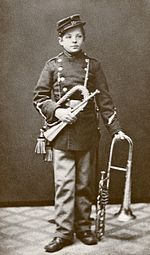 photograph of young Nielsen in band parade uniform with two brass instruments