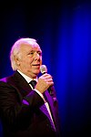 A man in a black tuxedo is holding a microphone and is facing right