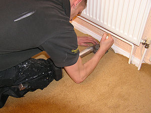 The carpet fitter is stretching a carpet onto ...