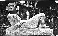 Black and white photograph of a stone carving of a human figure lying down with its knees bent and head turned