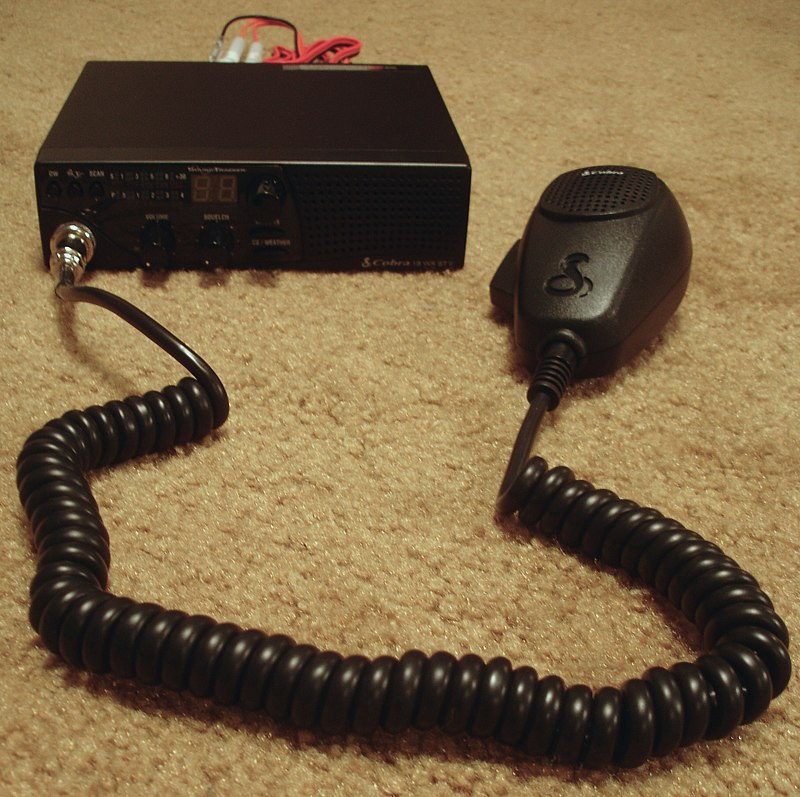 Small black mobile radio with hand-held microphone and long, coiled mic cord