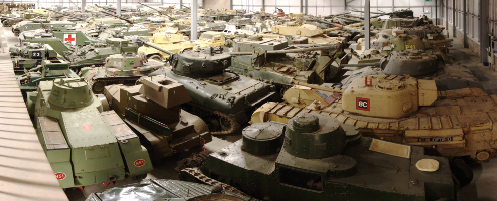Panorama of many dozen military vehicles in large warehouse.