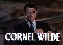 "Frame of a film. A man wearing a suit and tie is smiling towards the camera. The words ""CORNEL WILDE"" are superposed on the image across the bottom of the frame."
