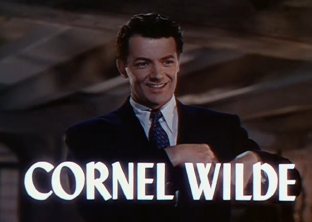 """Frame of a film. A man wearing a suit and tie is smiling towards the camera. The words """"CORNEL WILDE"""" are superposed on the image across the bottom of the frame."""