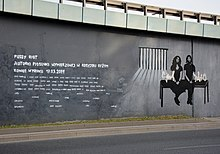 A stark black, white, and gray mural depicting two members of the group sitting on a bench with prison bars in the background.