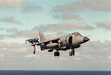 Grey jet aircraft with black radome and large engine inlet hovering with undercarriage extended. It is obscuring another identical jet in the distance. Near the bottom of the photograph, taken out at sea, is the horizon