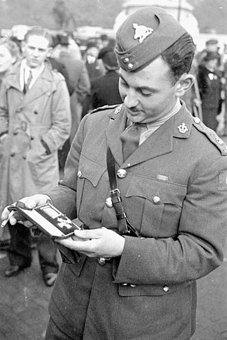 "Distinguished Service Order - Major Marie-Edmond Paul Garneau, of the Royal 22<sup>e</sup> Régiment, with the DSO he received for ""gallant and distinguished services in the combined attack on Dieppe"" after his investiture at Buckingham Palace in October 1942"