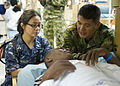 Defense.gov News Photo 110604-N-RM525-082 - U.S. Navy Lt. Cecilia Mendoza left and Rev. Juan Garcia a Roman Catholic priest from the Colombian Navy visit a patient during a tour aboard the.jpg