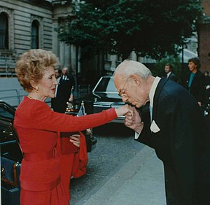 Hand-kissing - Denis Thatcher greets U.S. First Lady Nancy Reagan by kissing her hand, 1988.