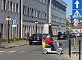 Disabled woman riding a bicycle path in an electric wheelchair, Tomaszów Mazowiecki, Saint Anthony Street, 2020.jpg