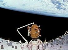 Una bahía de carga útil del transbordador espacial, cubierta con aislamiento blanco, con un pequeño módulo naranja cilíndrico en un extremo, sostenido por el brazo robótico del transbordador.  La negrura del espacio y la Tierra sirven como telón de fondo.