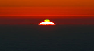 Optical phenomena - Green flash appears above the solar disc for a second or so. One such occurrence was taken from Cerro Paranal.